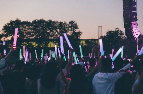 Students holding light sticks enjoying a concert
